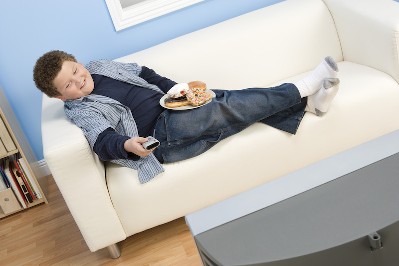 Overweight boy watching television on sofa